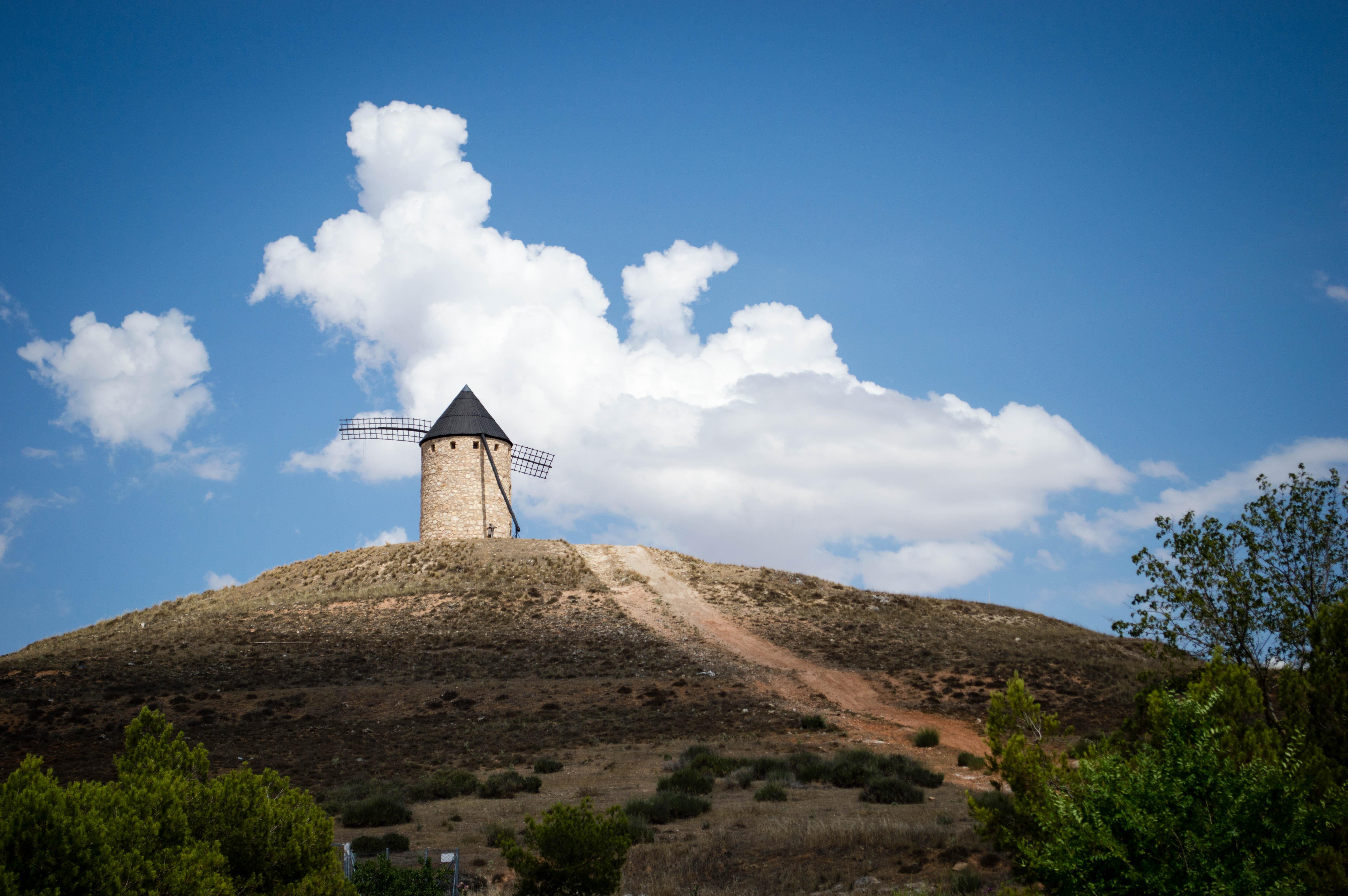 Un molino de viento frente a un camino de piedras en un día soleado en La Mancha