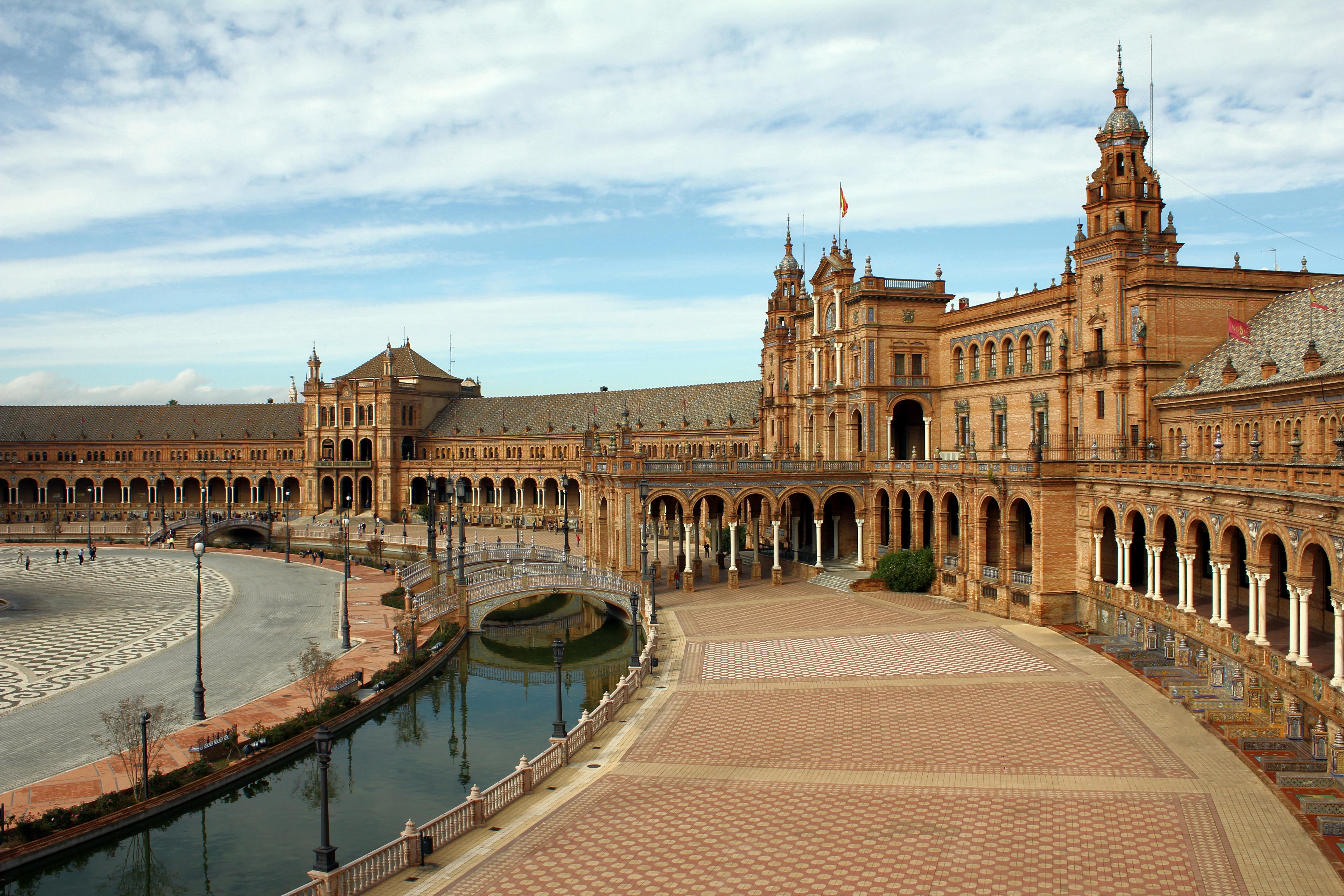 Fotografía de la plaza España en la ciudad andaluza de Sevilla, donde predomina el color marrón y el cielo está despejado