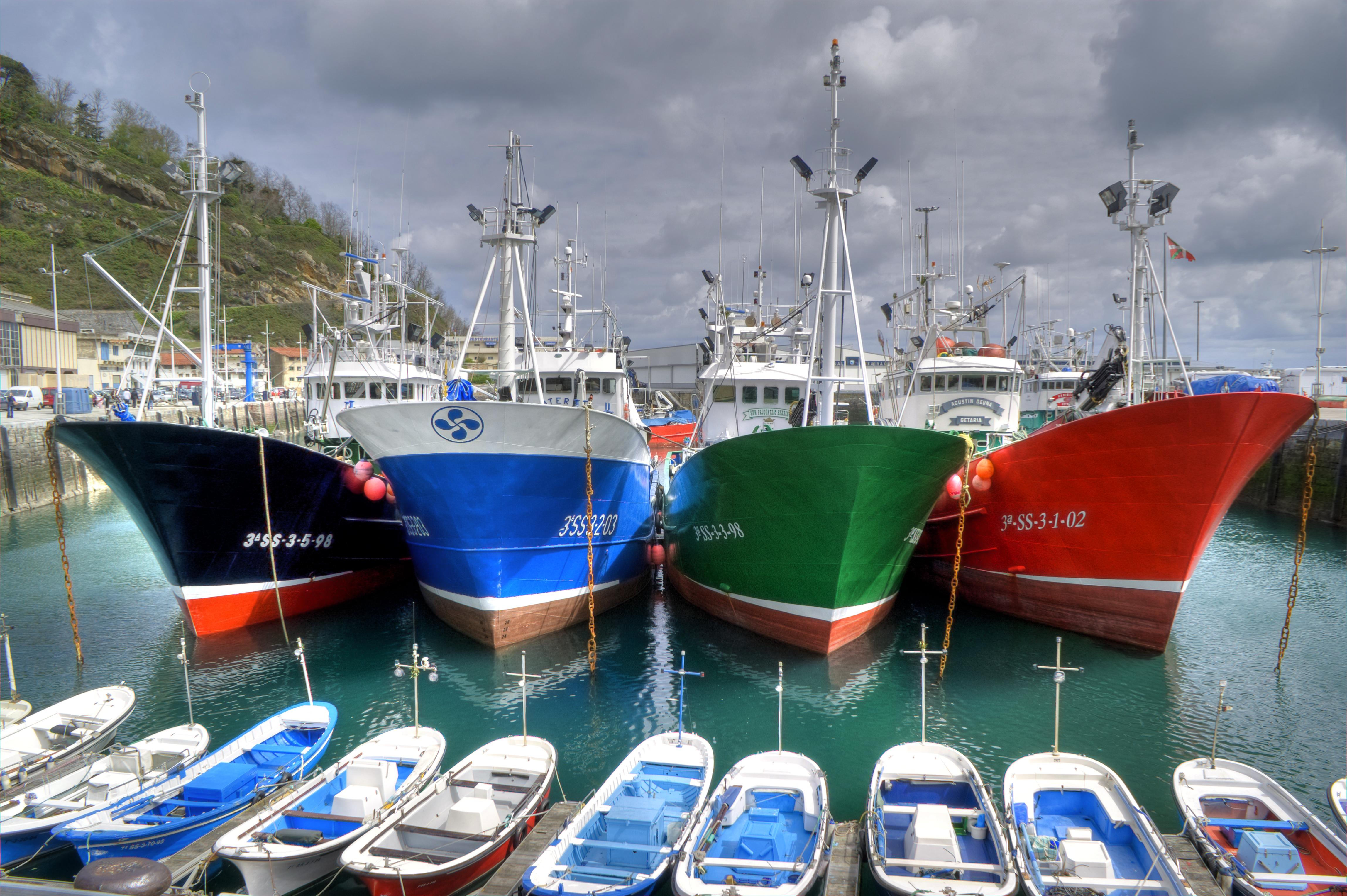 Cuatro barcos de pesca de color negro, azul, verde y rojo atracados en un puerto de la costa del país vasco, con el cielo nublado